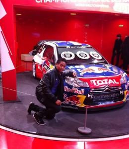 Frédéric Rabekoto posant devant la voiture de Sébastien Loeb